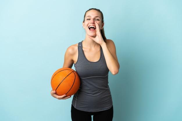 Молодая женщина, играющая в баскетбол, изолированная на синей стене, кричит с широко открытым ртом