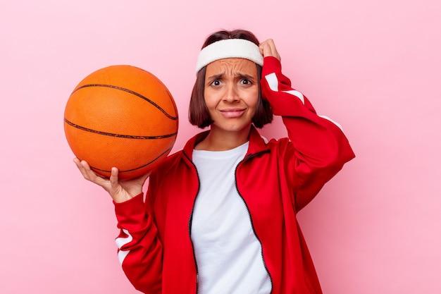ショックを受けているピンクの壁に隔離されたバスケットボールをしている若い女性、彼女は重要な会議を覚えています