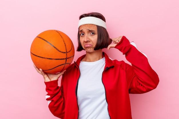 ピンクの壁に隔離されたバスケットボールをしている若い女性は、誇りと自信を持って、従うべき例を感じます