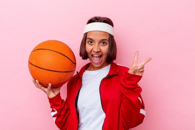 ピンクの壁に隔離されたバスケットボールをしている若い女性は、指で平和のシンボルを示して楽しくてのんき
