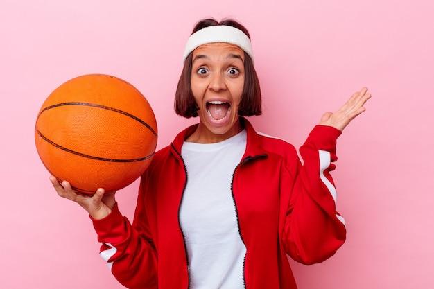 ピンクの壁に隔離されたバスケットボールをしている若い女性は、嬉しい驚きを受け取り、興奮し、手を上げる