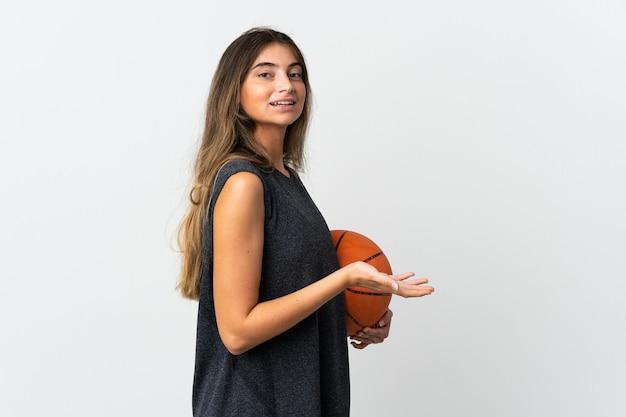 白い背景で隔離のバスケットボールをしている若い女性は、来て招待するために手を横に伸ばします