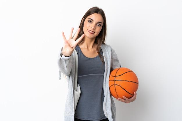 幸せな白い背景で隔離のバスケットボールをして、指で4を数える若い女性