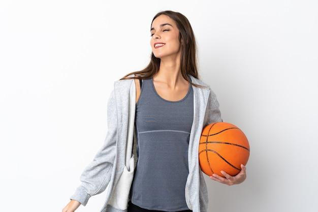 笑って白い背景で隔離のバスケットボールをしている若い女性