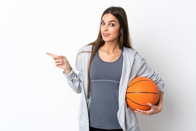 横に指を指している白い背景で隔離のバスケットボールをしている若い女性