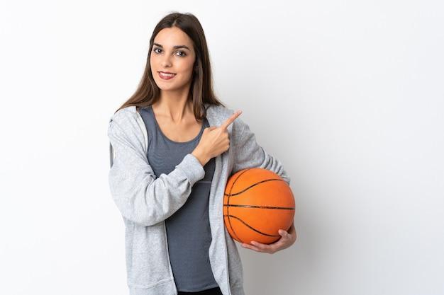 製品を提示する側を指している白い背景で隔離のバスケットボールをしている若い女性