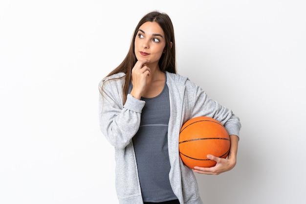 見上げながらアイデアを考えて白い背景で隔離のバスケットボールをしている若い女性