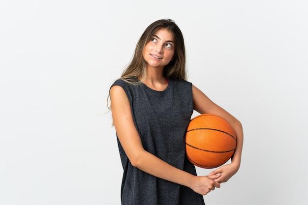 젊은 여자 농구를 찾는 동안 아이디어를 생각하는 흰색 배경에 고립