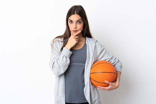 白い背景思考で隔離のバスケットボールをしている若い女性