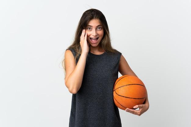 놀람과 충격 된 표정으로 흰색 배경에 고립 된 농구를하는 젊은 여자