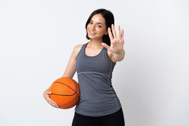 指で5を数える白で隔離バスケットボールをしている若い女性