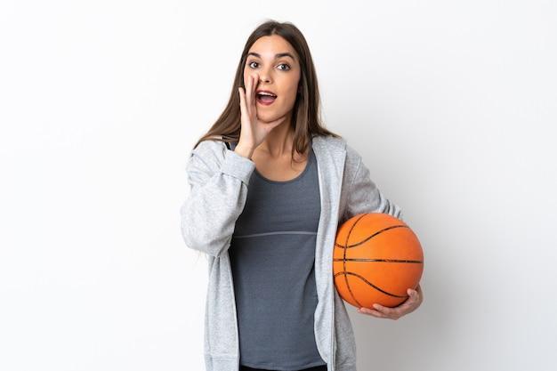 Молодая женщина, играющая в баскетбол, изолированная на белом, кричит с широко открытым ртом