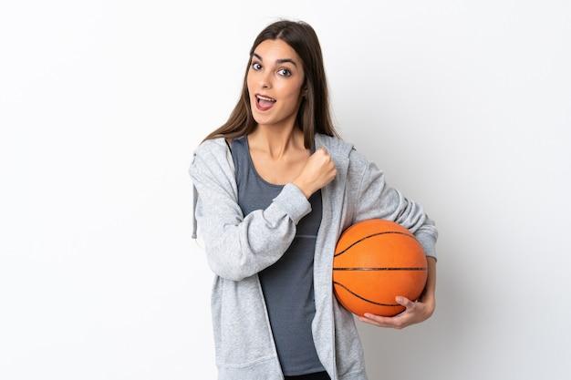Молодая женщина играет в баскетбол на белой стене празднует победу