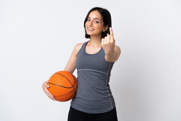 来るジェスチャーをしている白い壁に分離されたバスケットボールをしている若い女性