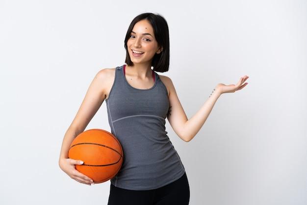 白い壁に隔離されたバスケットボールをしている若い女性は、来て招待するために手を横に伸ばします