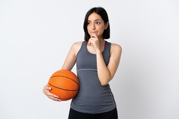 疑いと思考を持って白い壁に孤立したバスケットボールをしている若い女性