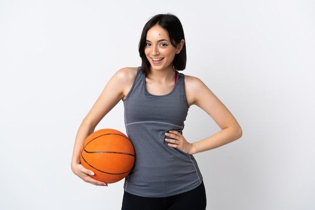 腰に腕と笑顔でポーズをとって白い壁に分離されたバスケットボールをする若い女性