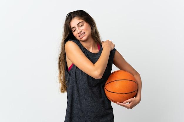 努力したために肩の痛みに苦しんでいる白い壁に隔離されたバスケットボールをしている若い女性
