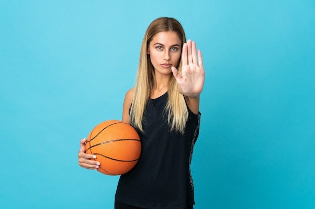 Young woman playing basketball isolated on white background making stop gesture