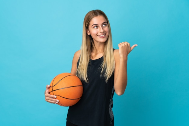 Young woman playing basketball isolated on white background pointing to the side to present a product