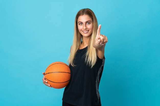Young woman playing basketball isolated on white background showing and lifting a finger