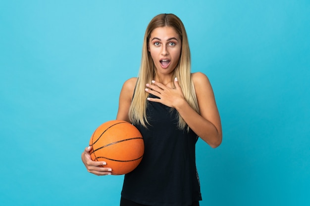 Young woman playing basketball isolated on white background surprised and shocked while looking right