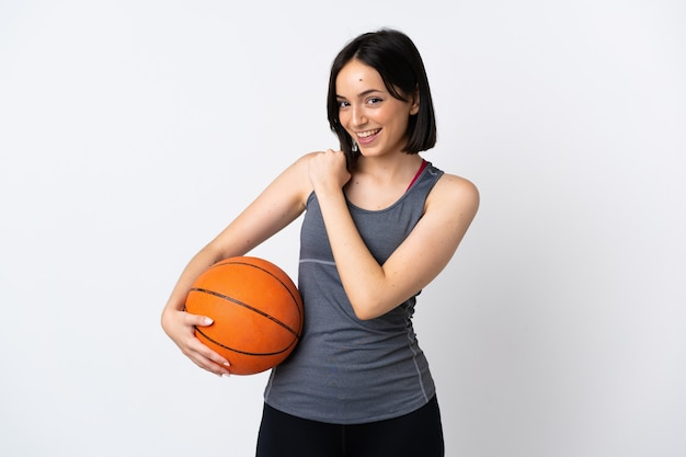 Young woman playing basketball isolated on white celebrating a victory