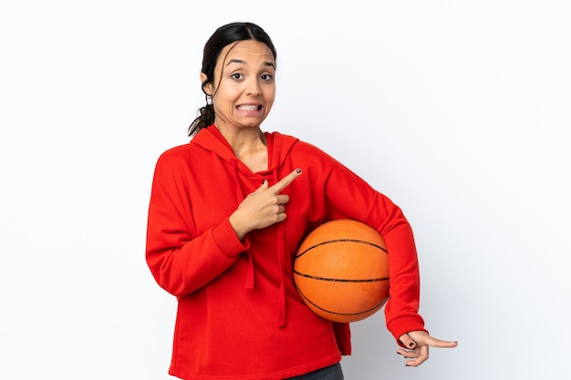 Young woman playing basketball over isolated white wall frightened and pointing to the side