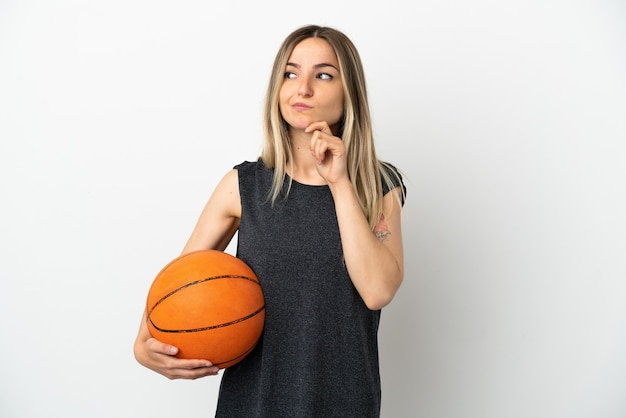 Young woman playing basketball over isolated white wall having doubts and thinking
