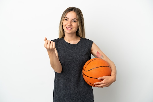 Young woman playing basketball over isolated white wall making money gesture