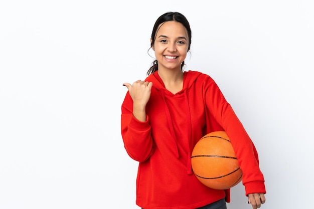 Young woman playing basketball over isolated white wall pointing to the side to present a product