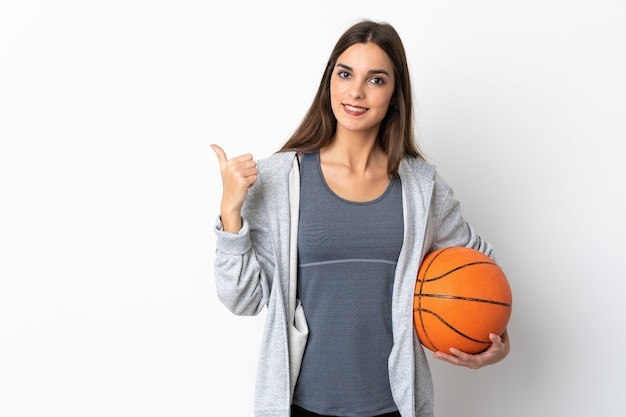 Young woman playing basketball isolated on white wall pointing to the side to present a product