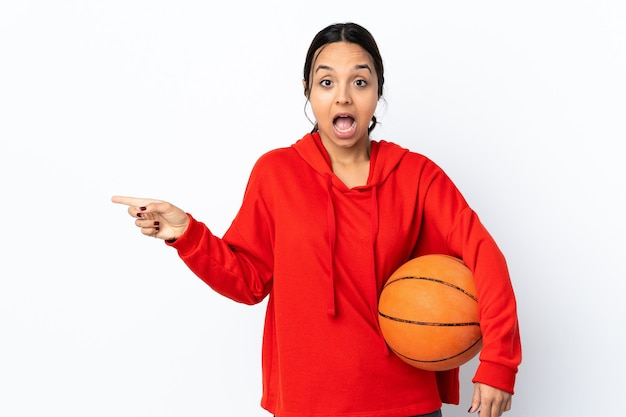 Young woman playing basketball over isolated white wall surprised and pointing side