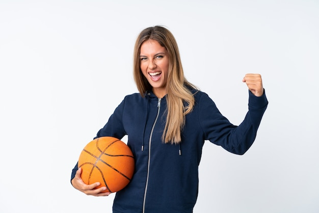 Young woman playing basketball over isolated white