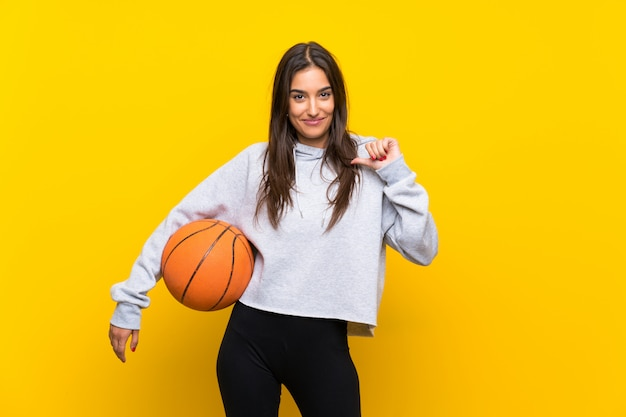 Young woman playing basketball  isolated on yellow  proud and self-satisfied