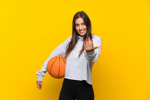 Young woman playing basketball over isolated yellow wall inviting to come with hand. happy that you came