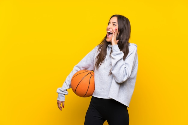 Young woman playing basketball over isolated yellow wall shouting with mouth wide open
