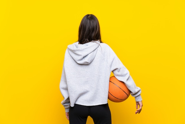 Young woman playing basketball over isolated yellow wall