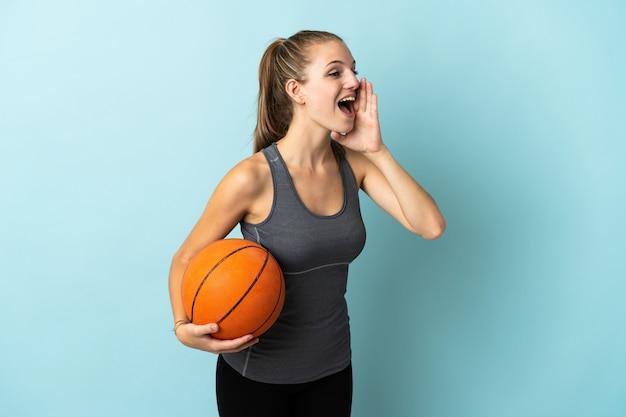 Молодая женщина играет в баскетбол на синем крике с широко открытым ртом в сторону