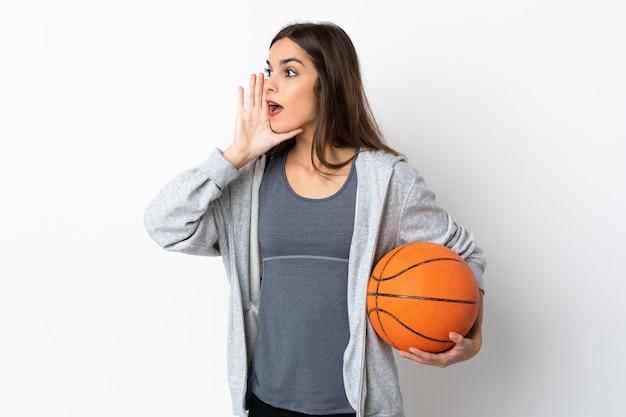 Молодая женщина играет в баскетбол на белом кричит с широко открытым ртом в сторону