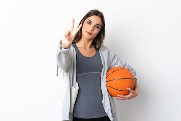 白い笑顔でバスケットボールをし、勝利のサインを示す若い女性