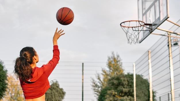 Молодая женщина играет в баскетбол на открытом воздухе с копией пространства