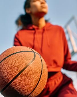 屋外でバスケットボールをする若い女性