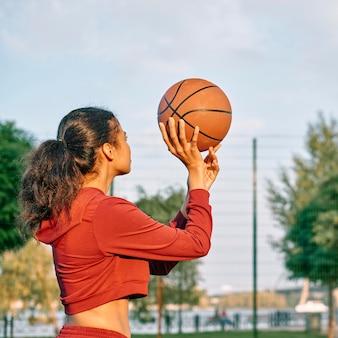 Молодая женщина играет в баскетбол на открытом воздухе