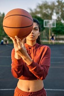 外でバスケットボールをしている若い女性