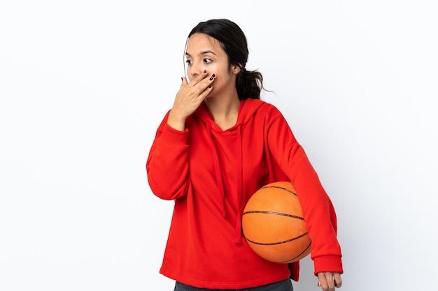 입을 덮고 측면을 찾고 격리 된 흰색 배경 위에 농구를하는 젊은 여자