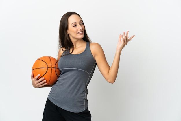 고립 된 흰색 배경 위에 농구를하는 젊은 여자가 와서 초대하기 위해 손을 옆으로 확장