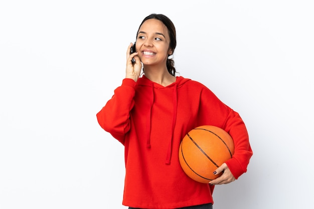 携帯電話との会話を維持している孤立した白い背景の上でバスケットボールをしている若い女性