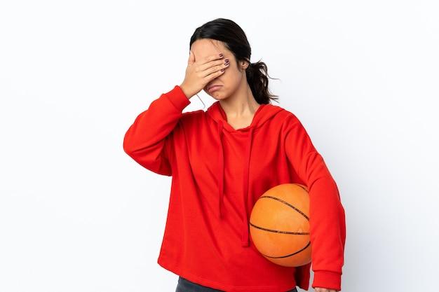정지 제스처를 만들고 얼굴을 덮고 격리 된 흰색 배경 위에 농구를하는 젊은 여자