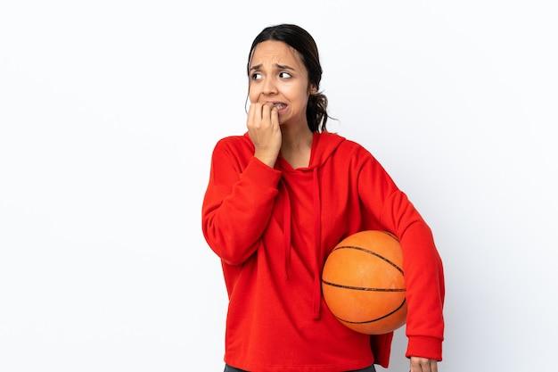 격리 된 흰색 배경 위에 농구를하는 젊은 여자 긴장하고 입에 손을 넣어 무서워